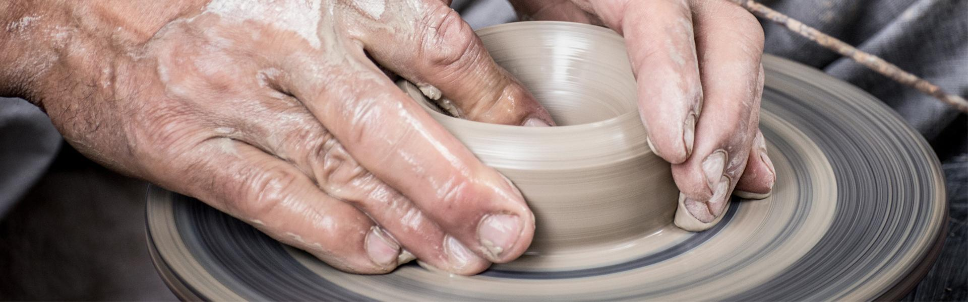 Using hand to form clay in to pottery on potter's wheel