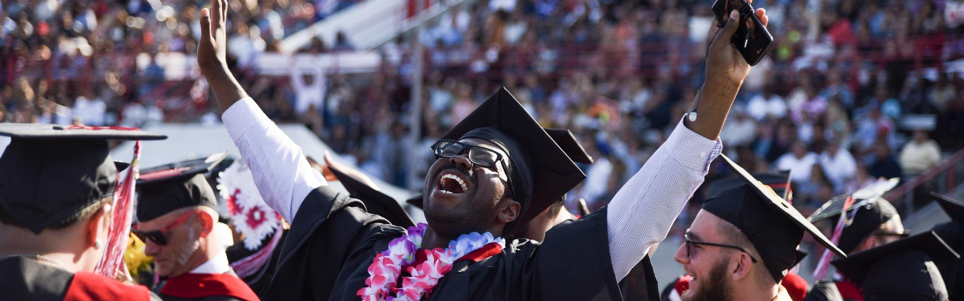 A black, college student cheering at his graduation.