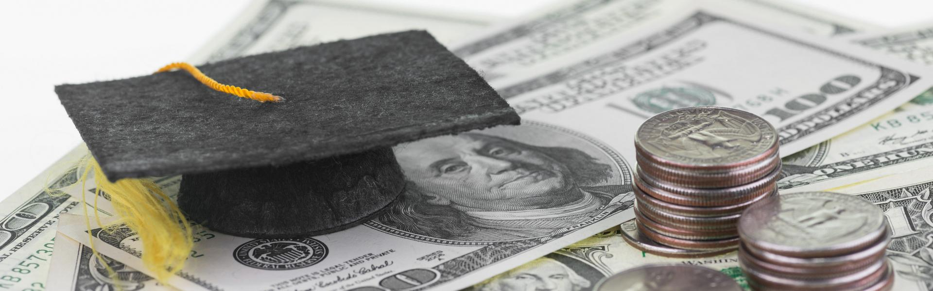 A graduation cap sitting on a pile of money.