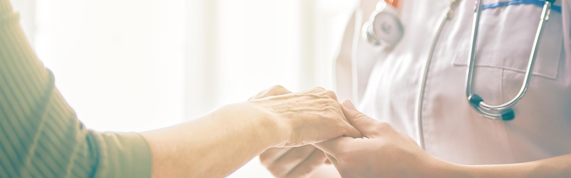 A nurse holding an elder's hand showing care