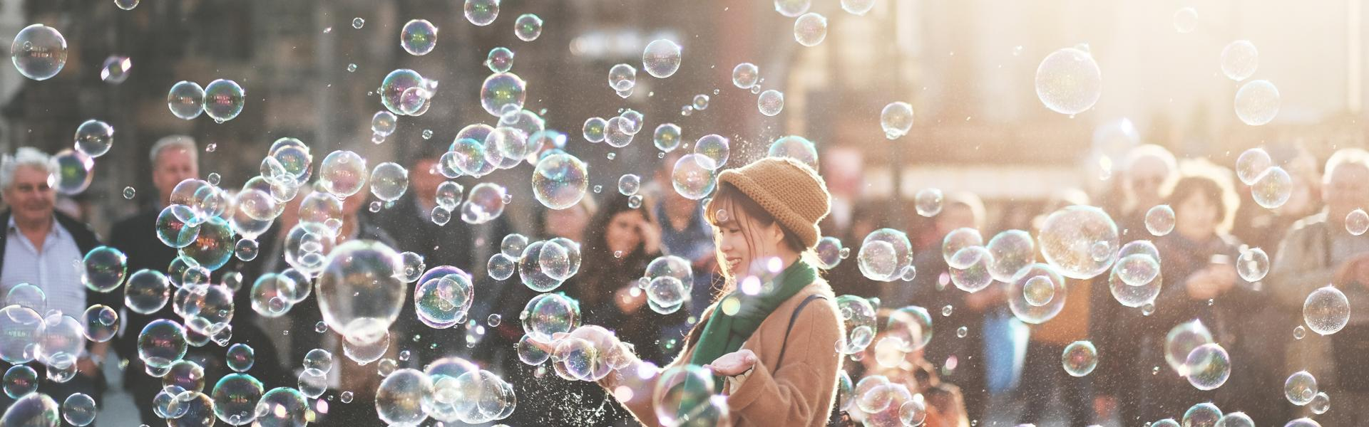 A woman standing in a crowd surrounded by bubbles.