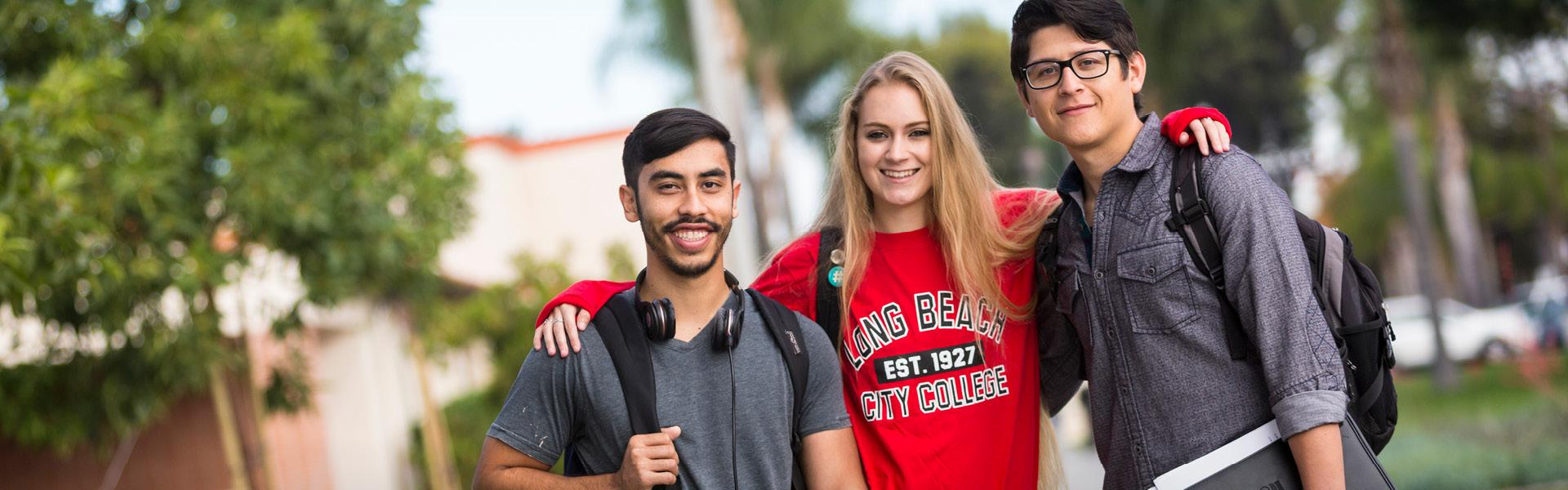 Three students standing together on campus.