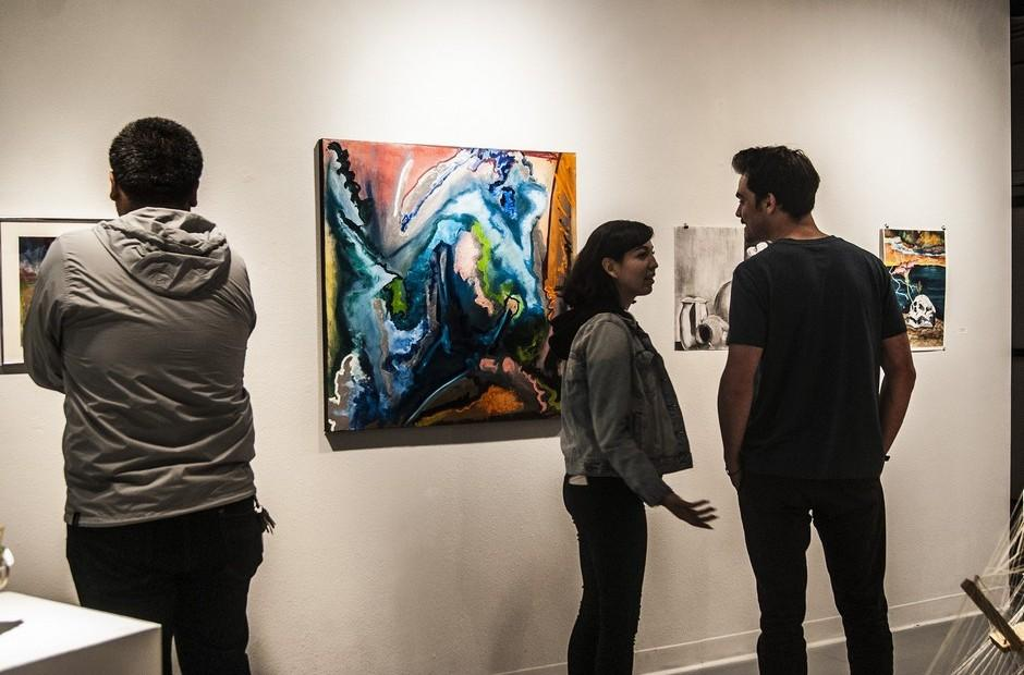 Several people looking at paintings on a wall.