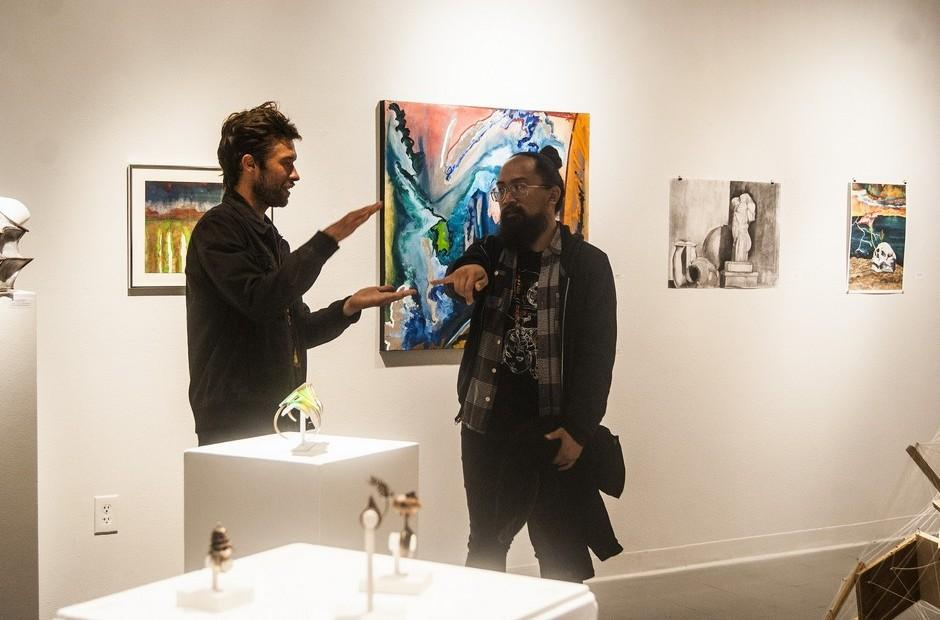 Two people discussing the artwork on display.