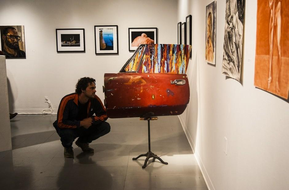 A man kneeling down to look at piece of artwork.