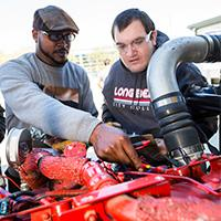 Two people working on automotive engine
