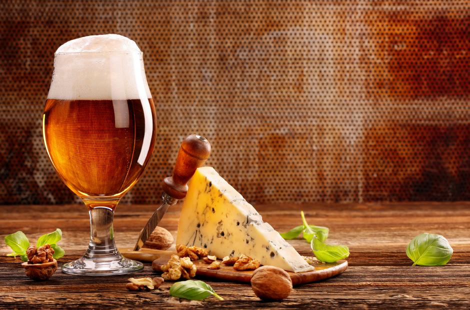 A glass of beer and a block of cheese.