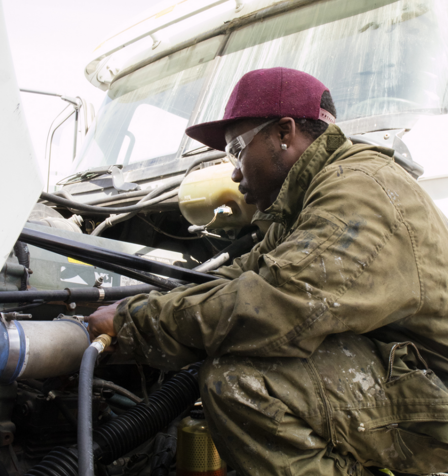 A black man working on the engine of a semi truck.