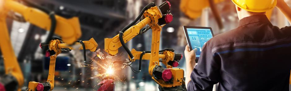 A men operating at Manufacturing Factory producing goods with Robotic Arms and computer device.
