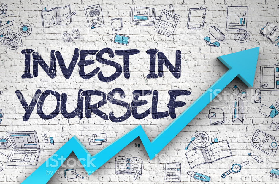 "The words ""Invest In Yourself"" written on a wall."
