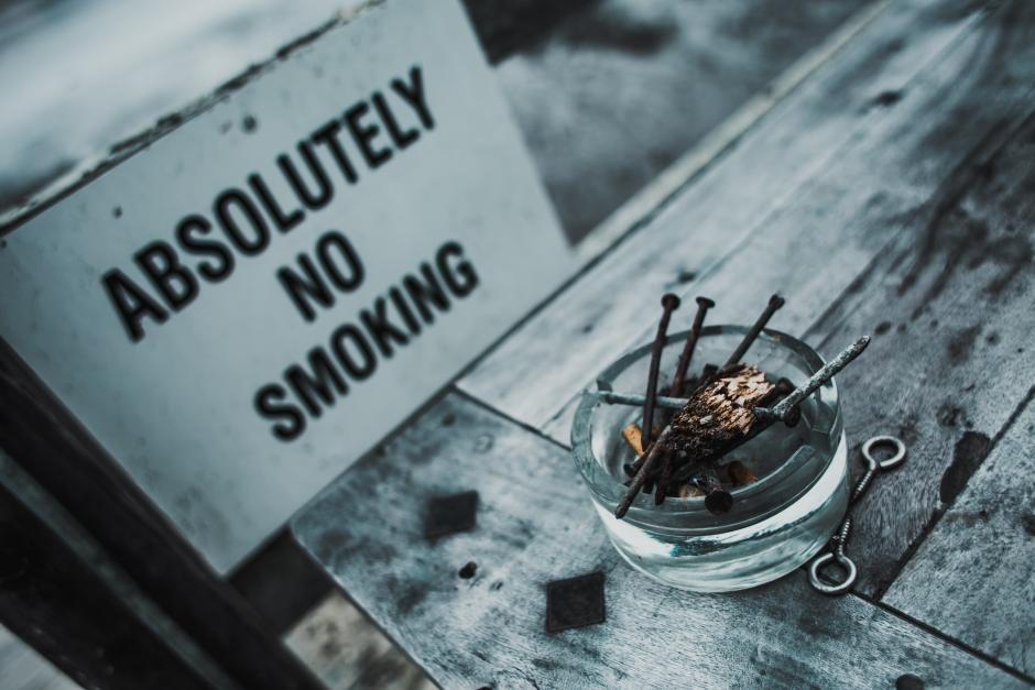An ashtray next to a no smoking sign.