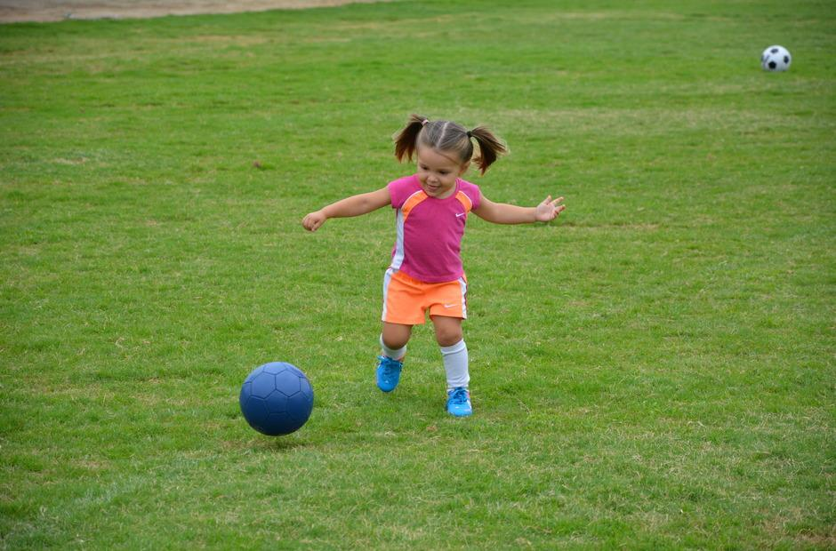 A young girl playing with a ball.