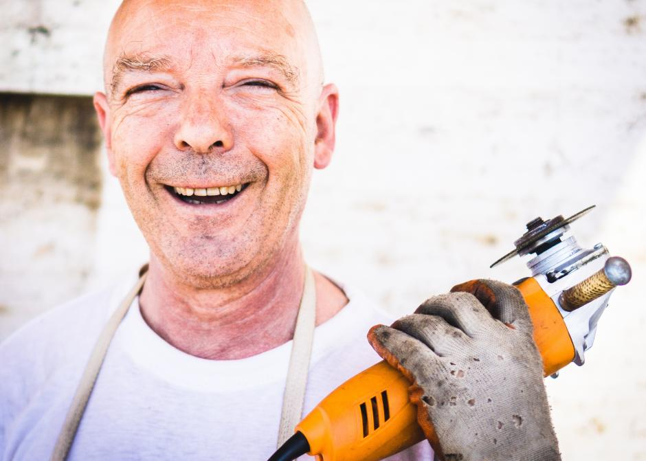 A man smiling and holding a tool