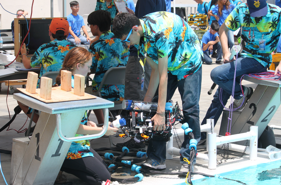 Students working on an underwater robot near a pool.