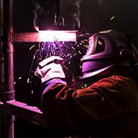 A person working on welding wearing a mask and gloves