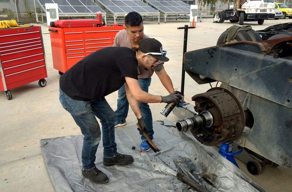 Two LBCC students repairing an alternative fuel vehicle.