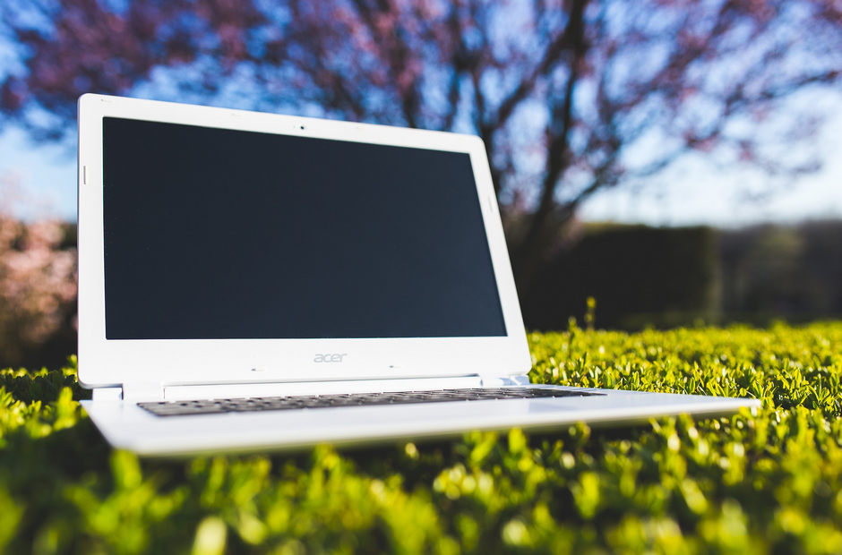 A picture of a laptop sitting on grass.