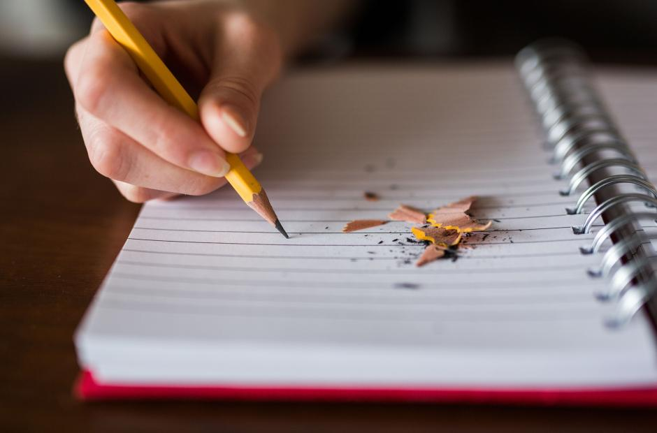 A person writing on a notepad.
