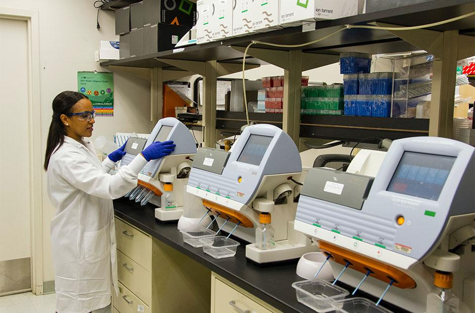 DNA Genotyping and Sequencing. A technician works among a fleet of desktop genomic sequencing machines at the Cancer Genomics Research Laboratory, part of the National Cancer Institute's Division of Cancer Epidemiology and Genetics (DCEG).