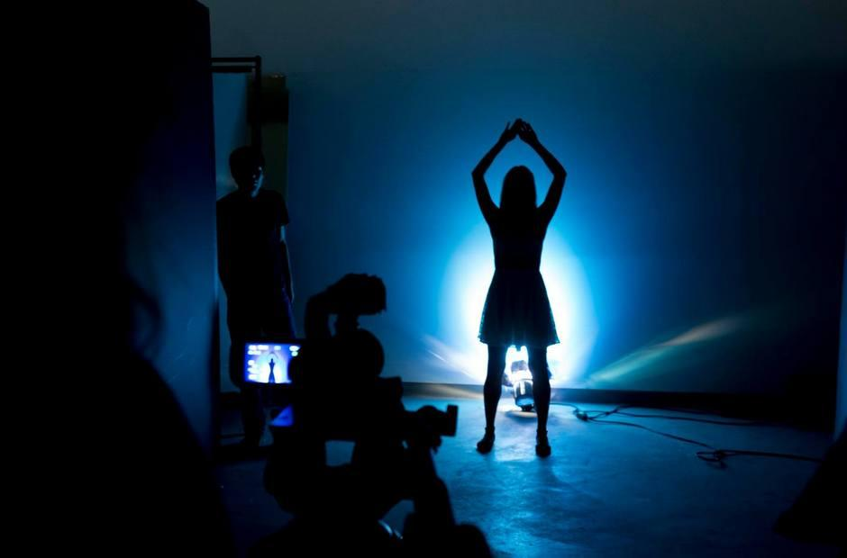 A student film being shot in dark room with blue light.