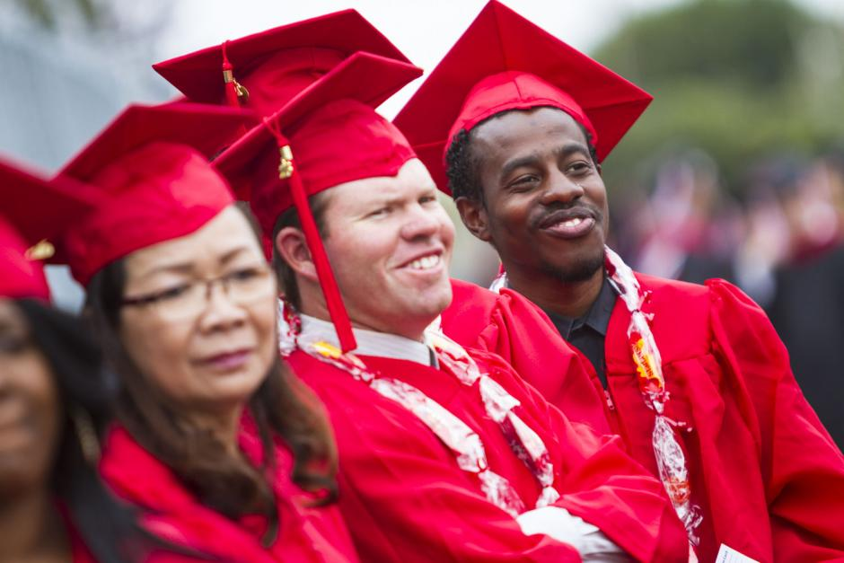 A group of LBCC students in their red graduation cap and gowns.