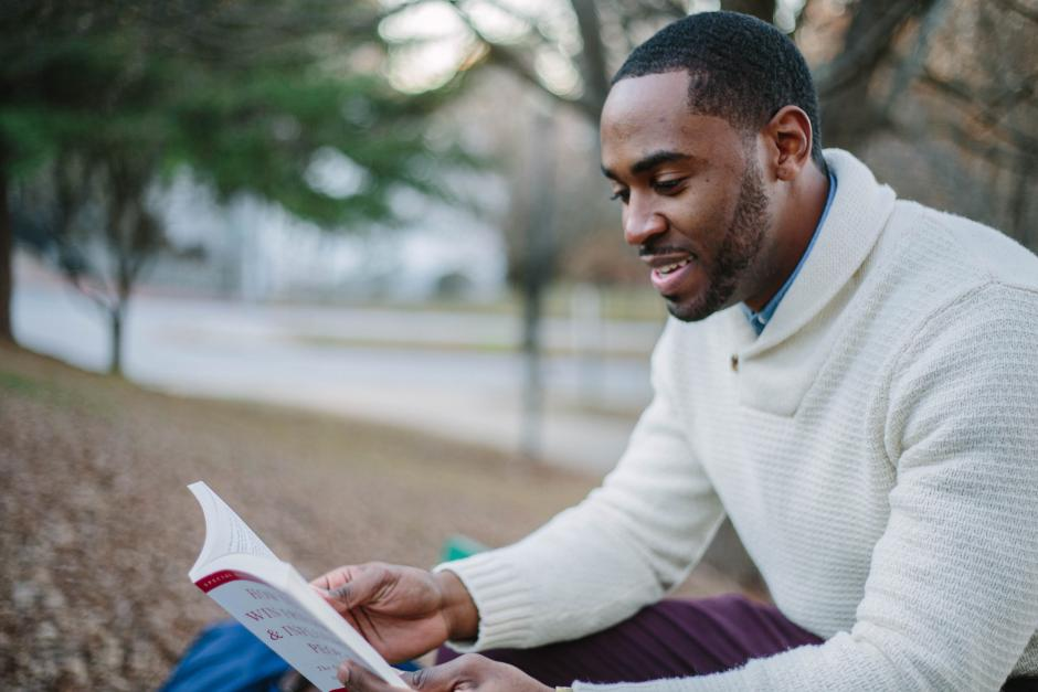 A young black man reading a book.