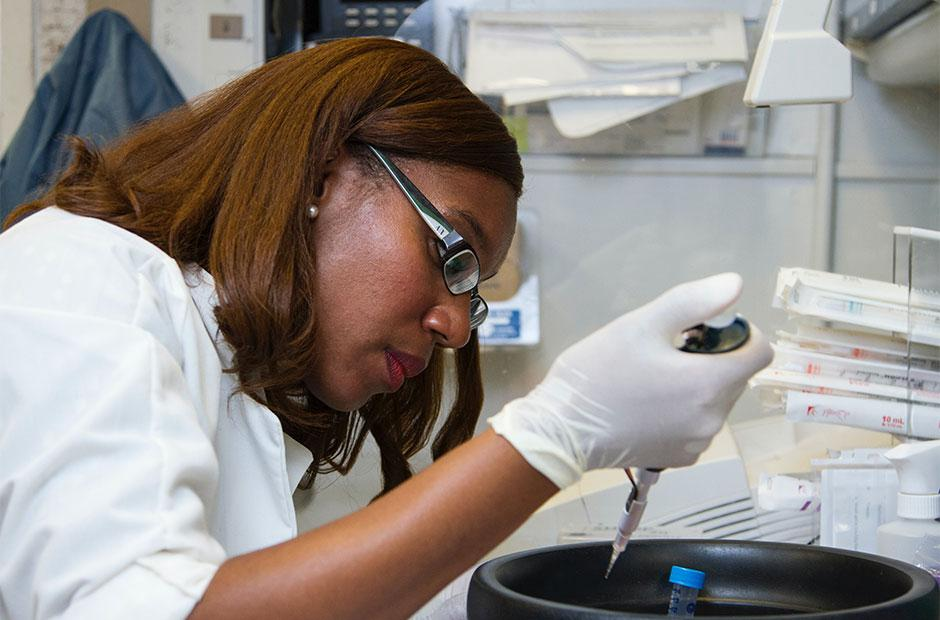 Chanelle Case Borden, Ph.D., a postdoctoral fellow in the National Cancer Institute's Experimental Immunology Branch, pipetting DNA samples into a tube for polymerase chain reaction, or PCR, a laboratory technique used to make multiple copies of a segment of DNA.