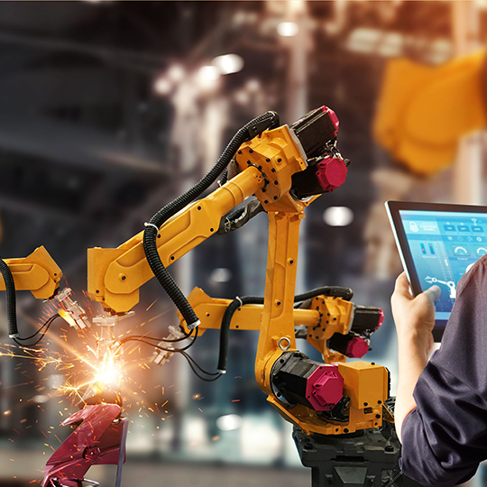 Advanced Manufacturing Technology with robotic arms and technicians operating machines with computer pad