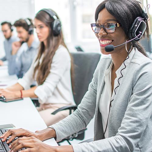 Smiling young woman with headset working in call center