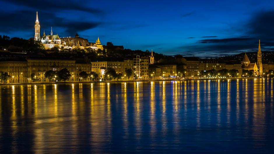 The city of Budapest at night on the Danube River.