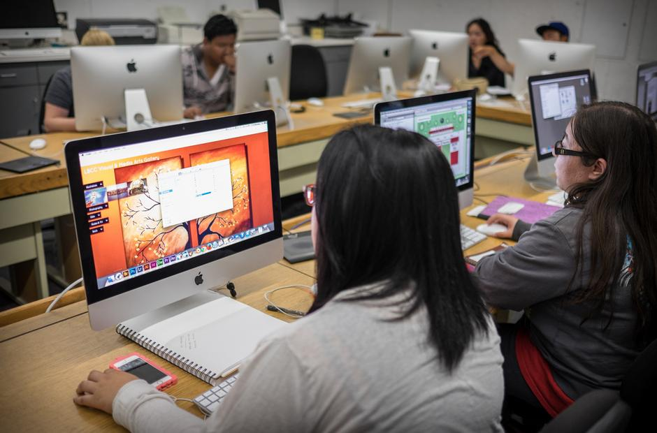 A group of students working on graphic design projects in a computer lab.