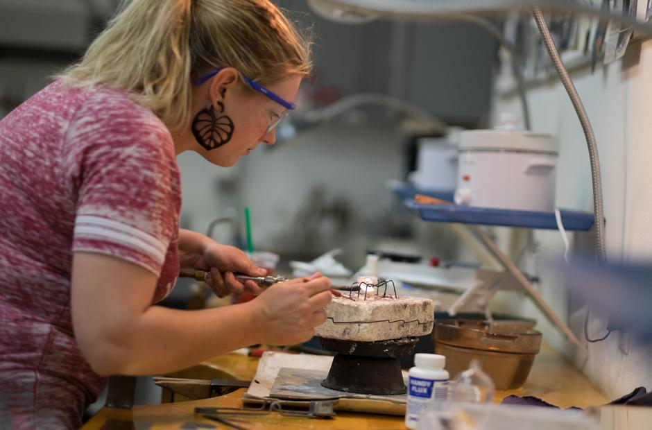 A student carefully shapes metals used in custom jewelry.