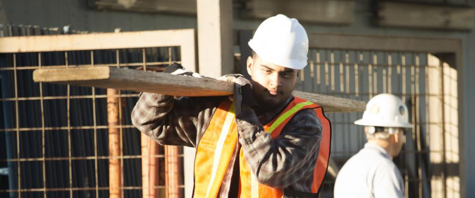 A construction worker carrying a 2x4.
