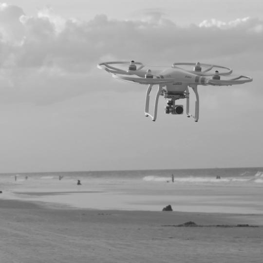 A picture of a drone flying at the beach