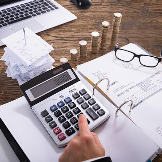 Close-up Of A Businessperson Calculating Invoice