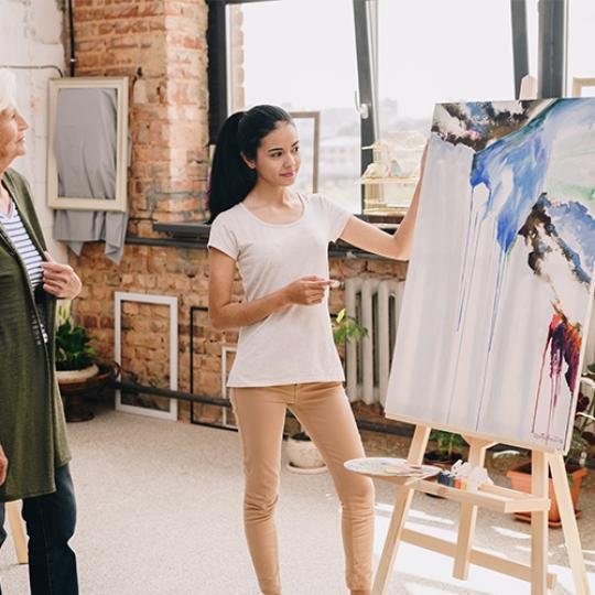 Artist explaining her art in a studio