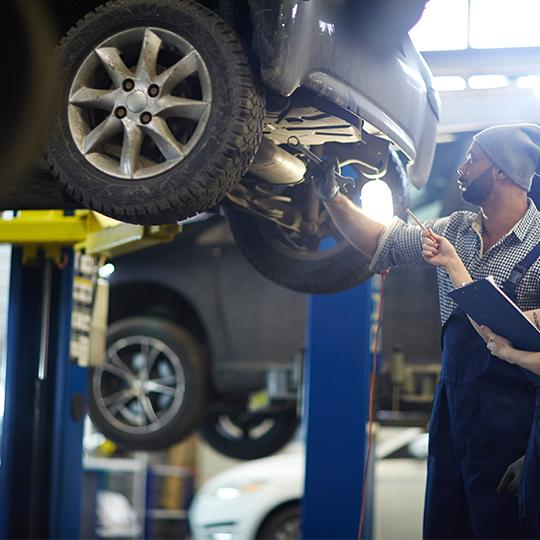 Auto Mechanics performing services in autoshop